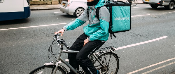 Oxford United Kingdom Mar 3 3017 Side view of young male cyclist delivering food fast to client via Deliveroo App commuting fast in the university city with big thermo bag with Deliveroo logo